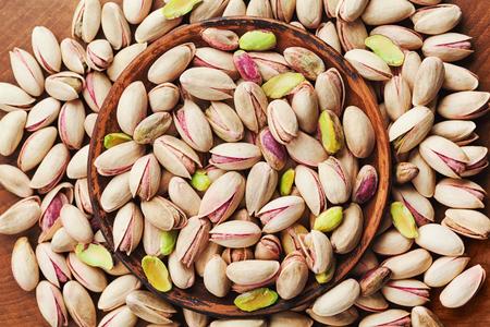Kom pistachenoten op houten tafelblad bekijken. Gezond eten en een snack.