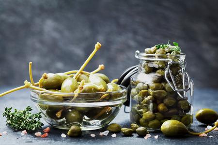 Gemengde kappertjes in pot en kom op donkere keukentafel. Stockfoto