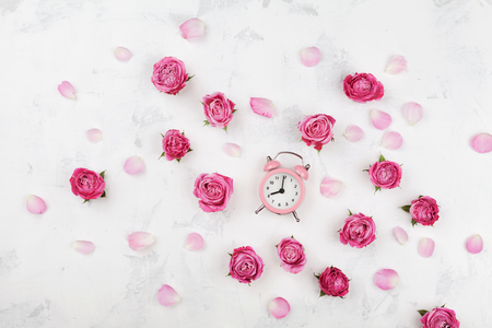 Pink rose flowers, petals and alarm clock on white desk from above in flat lay style. Wake up concept. Stock Photo