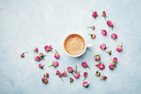 Morning coffee cup and dry rose flowers on blue vintage table top view in flat lay style. Cozy breakfast on Mother or Woman day. Stock Photo