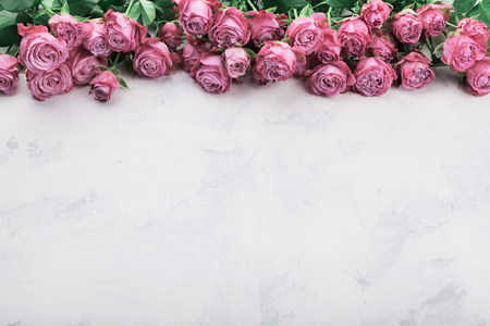 Vintage rose flowers on white stone table. Floral border. Empty space for text.