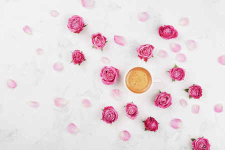 Morning coffee cup, petals and beautiful pink rose flowers on white stone table top view in flat lay style. Cozy breakfast on Mother or Woman day.