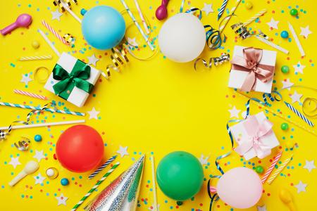 Verjaardag partij achtergrond of frame met kleurrijke ballon, geschenk, confetti, zilveren ster, carnaval cap, snoep en streamer. Vlakke lay-stijl. Vakantievlieger met exemplaarruimte.