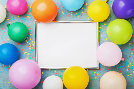 Colorful balloons, silver frame and confetti on blue background top view. Birthday or party mockup for planning. Flat lay style. Copy space for text. Foto de archivo
