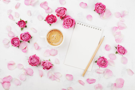 Morning coffee mug for breakfast, empty notebook, petal and pink rose flowers on white table top view in flat lay style. Foto de archivo