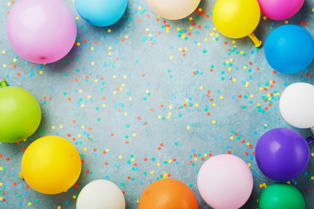 Colorful balloons and confetti on turquoise table top view. Birthday, holiday or party background. Flat lay style. Empty space for text.