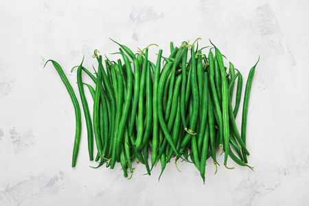 Bunch of green or string beans in rustic bowl on white table from above. Stock Photo