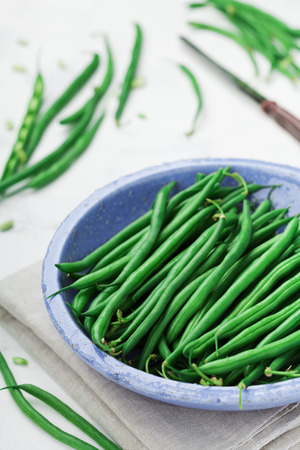 snap bean: Harvest of green or string beans in rustic bowl on white table.