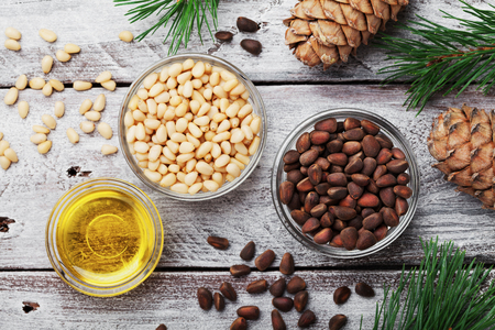 Pine nuts, oil and cedar cones on rustic wooden background top view. Organic and healthy superfood. Stock Photo