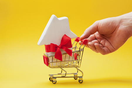 Man holding hand shopping cart with small white house decorated red bow ribbon on yellow background. Buying a new home, gift or sale of real estate concept.