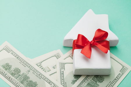 Small white house decorated red bow ribbon and dollars money on green background. Buying a new home, gift or sale of real estate concept.