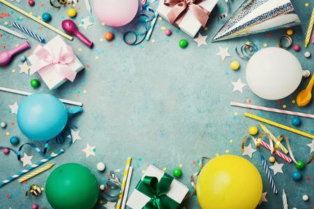 Vakantiekader of achtergrond met kleurrijke ballon, cadeau, confetti, zilveren ster, carnaval cap, snoep en streamer. Vlakke lay-stijl. Verjaardag of partij wenskaart met kopie ruimte.