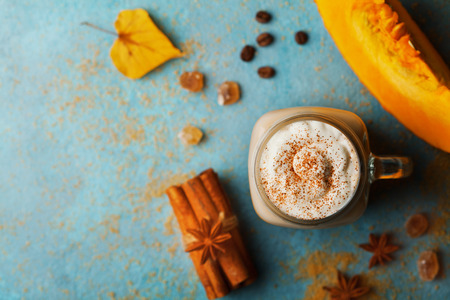 Pumpkin spiced latte or coffee in cup decorated cinnamon on turquoise vintage table top view. Autumn, fall or winter hot drink. Cozy breakfast.