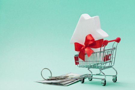 Small shopping cart with white house model decorated red bow ribbon, dollars money and bunch of keys on green background. Buying a new home, gift or sale of real estate concept.