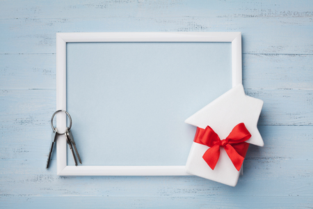 Miniature white house decorated red bow ribbon, frame and keychain on blue wooden background. Buying a new home, planning housewarming, gift or sale of real estate concept.