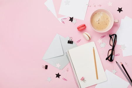 Coffee, macaron, office supply and clean notebook on pink pastel table top view for blogging. Flat lay style. Beautiful morning breakfast. Fashion woman working desk.