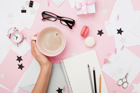 Female hand with coffee cup, macaron, office supply, gift and notebook on pastel desk top view. Fashion pink woman workplace background for blogging. Flat lay. Beautiful morning breakfast. Stock Photo