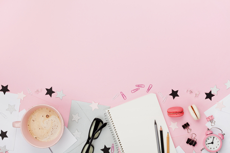 Fresh coffee, macaron, office supply, alarm clock and notebook on pink pastel table top view. Flat lay style. Cozy morning breakfast. Fashion woman working desk for blogging.