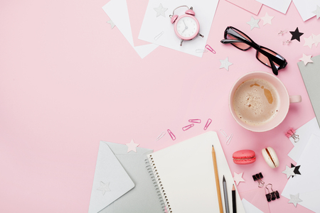 Cup of coffee, macaron, alarm clock, office supply and clean notebook on pink pastel table top view. Flat lay. Beautiful morning breakfast. Fashion woman blogger working desk. Stockfoto