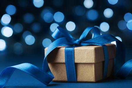 크리스마스 선물 상자 또는 파란색 bokeh 배경에서 현재입니다. 휴일 인사말 카드입니다. 스톡 콘텐츠