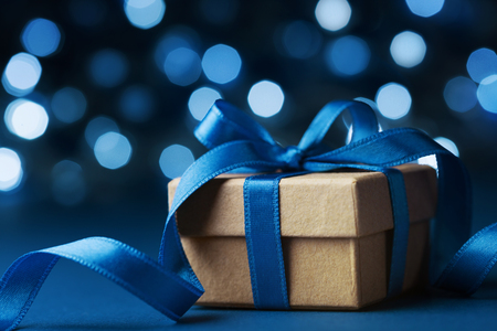 Christmas gift box or present against blue bokeh background. Holiday greeting card.