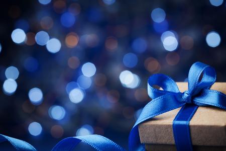크리스마스 선물 상자 또는 마법의 파란색 bokeh 배경에 활 리본 메뉴와 함께 존재합니다. 인사말 텍스트를위한 공간을 복사합니다.