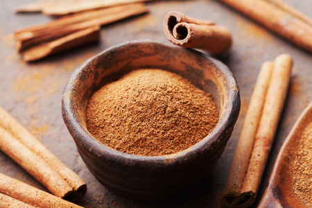 Whole cinnamon sticks and powder on brown rustic background. Aromatic spices.