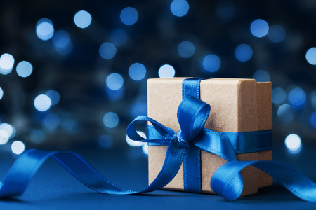 Holiday gift box or present with bow ribbon against blue bokeh background. Magic christmas  greeting card.