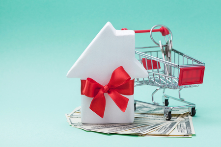 Miniature shopping cart, small white house decorated red bow ribbon, dollars money and keychain on green background. Buying a new home, gift or sale of real estate concept.