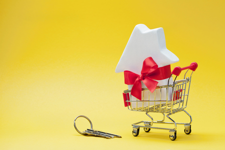 Shopping cart with small white house decorated red bow ribbon and bunch of keys on yellow background. Buying a new home, gift or sale of real estate concept.