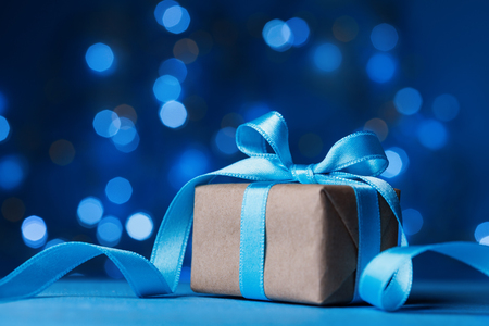 Holiday greeting card. Christmas gift box or present with bow ribbon on magic turquoise bokeh background.