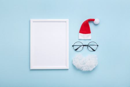 Picture frame, santa hat, beard and glasses on blue background top view. Creative christmas mockup. Greeting card, invitation or flyer. Flat lay.  Stock Photo