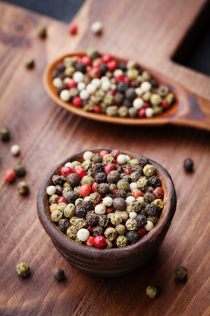 spiciness: Peppercorns whole in rustic bowl on wooden board. Macro shot. Stock Photo