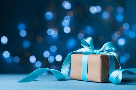 Christmas gift box or present with bow ribbon on magic blue bokeh background. Copy space for greeting card. Reklamní fotografie - 90434310