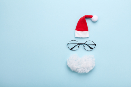 Creative Christmas composition. Greeting card, invitation. Santa hat, beard, and glasses on blue background top view. Flat lay.