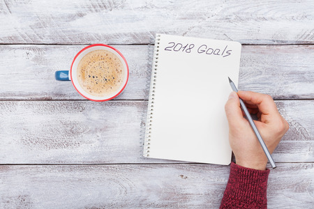 Male writing goals for 2018. Planning concept. Top view. Foto de archivo