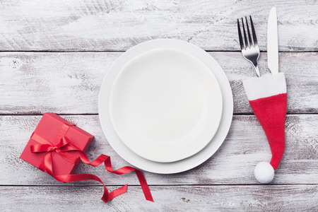 Empty white plate and decoration on wooden rustic table top view. Christmas table setting concept. Stock Photo