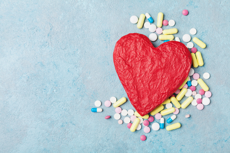Red shape of heart and colorful drug pills on blue background top view. Pharmaceutical, cardiology and health care concept.
