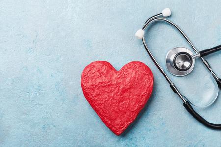 Rode hartvorm en medische stethoscoop op blauwe hoogste mening als achtergrond. Gezondheidszorg, medicare en cardiologie concept.