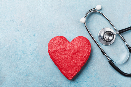 Red heart shape and medical stethoscope on blue background top view. Health care, medicare and cardiology concept.