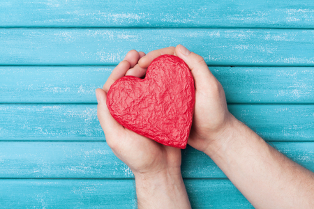 Red heart shape in hands top view. Healthy, donation organ, donor, hope and cardiology concept. Valentines day card. Stock Photo