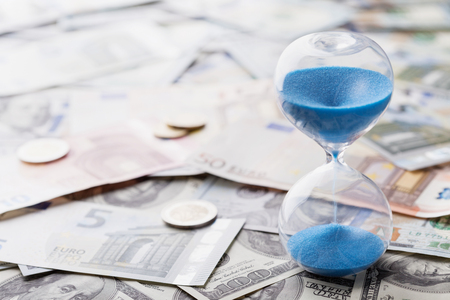 Different currency and hourglass. Payment, banking and money concept.  Stock Photo