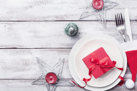 Christmas table setting. Gift box, fir tree, white plate and silverware on rustic table top view. Preparation for holiday dinner. Stock Photo