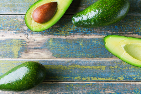 Fresh green avocado on vintage wooden table top view. Organic wellness food background. Copy space for text.