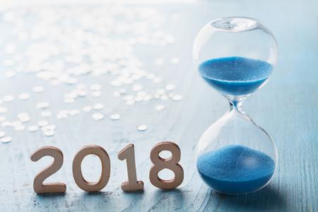 Grußkarte des neuen Jahres 2018. Sanduhr oder Sanduhr auf blauem Holztisch.