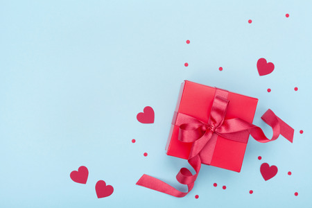 Present or gift box, paper heart and confetti on blue background top view. Valentines day greeting card. Flat lay style.