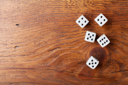 Heap of white dice on rustic wooden table top view. Gambling devices. Game of chance concept. Stock Photo