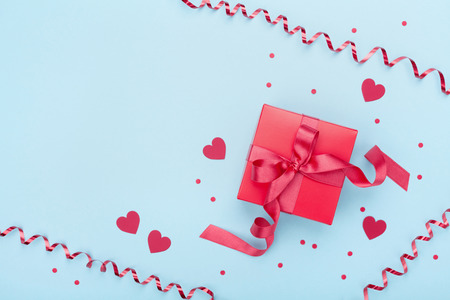 Red gift box, serpentine, hearts and confetti on blue background top view. Valentine's day greeting card. Flat lay.