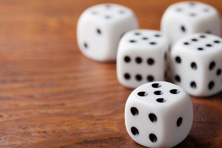 Dice on rustic wooden table. Gambling devices. Game of chance concept. Macro shot.