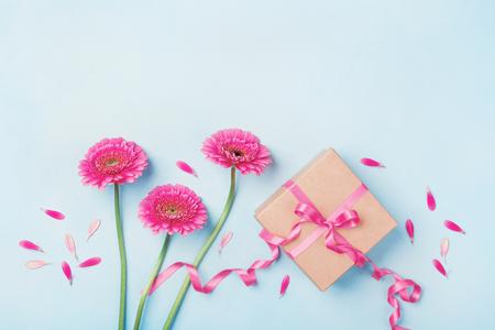 Composition de printemps avec des fleurs roses et boîte de cadeau sur la vue de dessus de table bleu. Carte de voeux pour l'anniversaire, la femme ou la fête des mères. Plat poser. Banque d'images